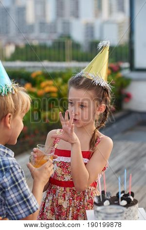 Pretty dark-haired little girl gesticulating and talking to her best friend while having fun at outdoor birthday party
