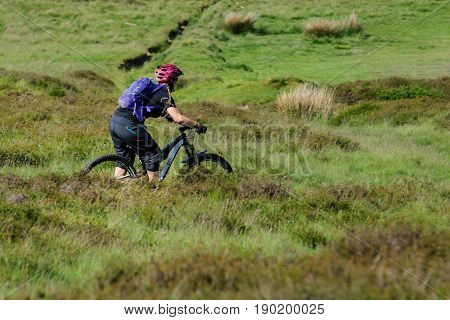 Llantysilio Wales UK - June 4 2017: A female mountain biker makes her way across the rugged terrain at the Horseshoe Pass near Llangollen a popular spot for walkers and cyclists