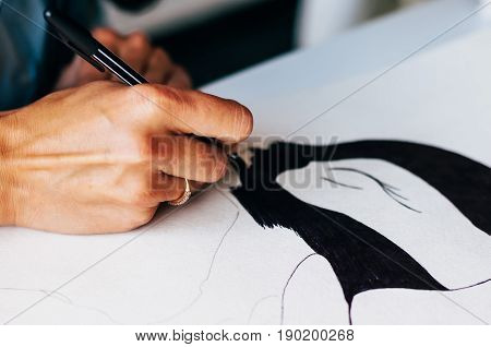 Female hand drawing a picture by black pen on paper. Close-up. Unrecognizable woman drawing a picture.