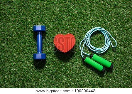 Top View Of Colorful Dumbbell With Heart Symbol And Skipping Rope On The Grass