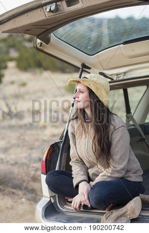 Caucasian woman smiling in trunk of car