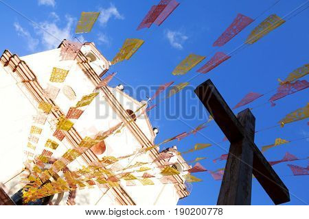 Low angle view of cross, prayer flags and church, San Cristobal de Las Casas, Chiapas, Mexico