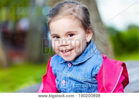 Portriat of cute little smilling child girl in a park