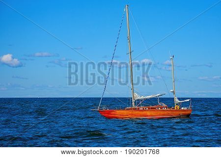 Yacht with lowered sail back to port
