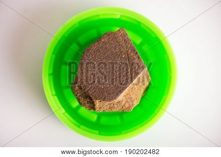 Macro detail of a single piece of cannabis extraction aka hashish isolated over white background