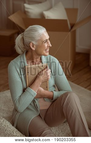 Happy Senior Woman Smiling And Hugging Photo In Frame While Sitting On Floor