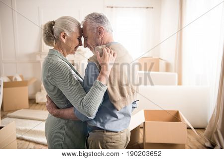 Side View Of Happy Senior Couple Hugging And Looking At Each Other