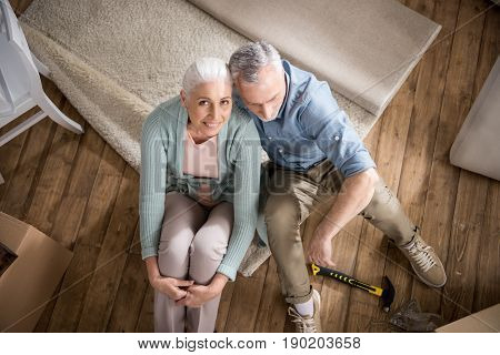 Sweetheart Senior Couple Embracing While Sitting On The Floor At Home