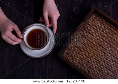 womans hands with cup of tea and rattan tray dark tones