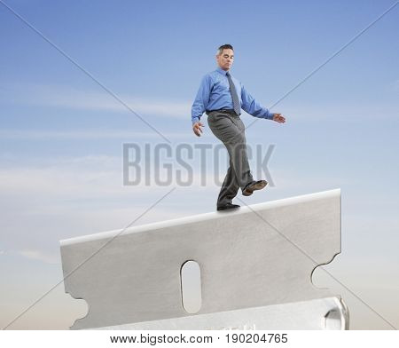 Mixed race businessman walking on razor edge