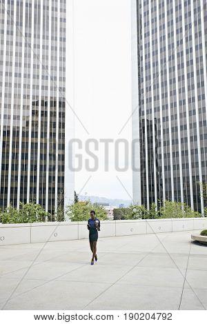 African American businesswoman walking on city street