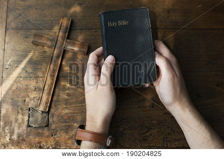 Hands Holding Holy Bible with Wooden Cross