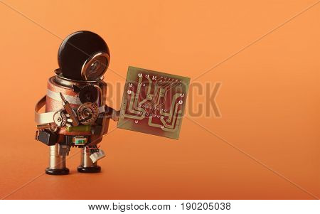 Computer upgrade automation concept. Robot with abstract circuit chip. retro style toy cyborg, black helmet head, electronic accessories body. Orange background copy space photo