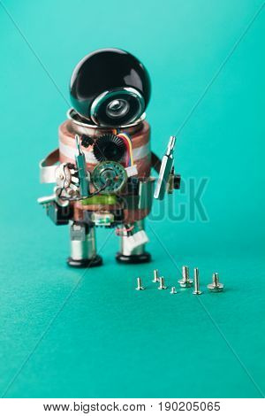 Electrician worker and different size screws. Repair man robot with screw driver. Fun toy character, black helmet head. Macro view, shallow depth of field, greenery background, copy space