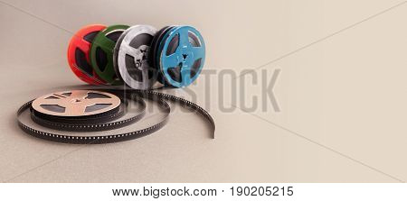 Vintage collection 8 mm cinema film reel. Retro design colorful celluloid accessories for home video projector. Gray background, selective focus.