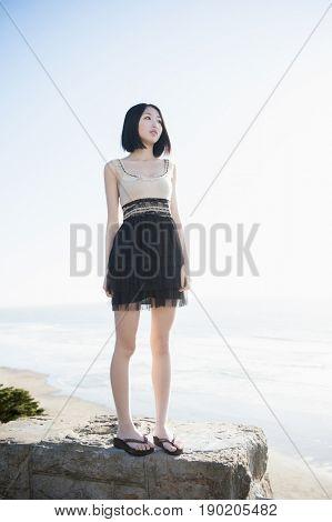 Glamorous Chinese woman standing on rock near beach