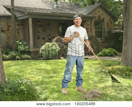 Native American man raking front yard