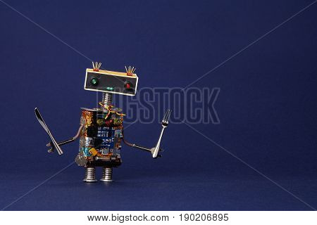 Friendly robot waiter with fork and knife. Food menu concept cute cooking kitchen chef toy character on dark blue textured paper copy space