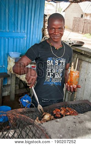 GRAND BASSAM, IVORY COAST, AFRICA. May 1, 2013. Young African man cooks meat on a grill in a beach side cafe in Grand Bassam.
