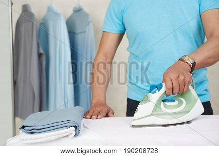 Cropped image of bachelor ironing his clothes in the morning