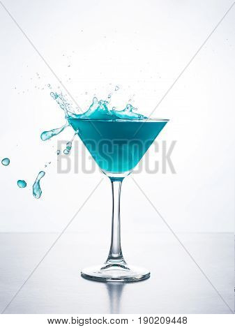 Blue cocktail in martini glass with ice cube splashing into liquid against white background. Blue curacao cocktail with splash on white.