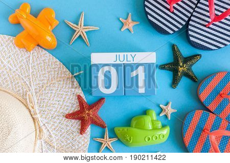 July 1st. Image of july 1 calendar with summer beach accessories and traveler outfit on background. Summer day, Vacation concept.