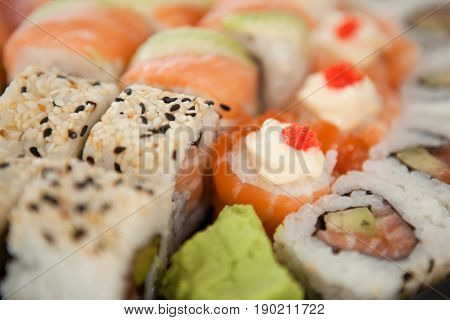 Close-up of assorted sushi set served in white box against white background