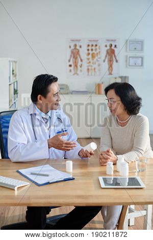 Wait-up portrait of friendly doctor sitting at desk and prescribing drugs to pretty senior patient