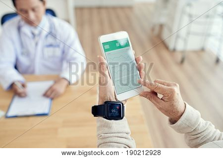 Close-up shot of wrinkled hands using activity tracker and smartphone in order to check heart rate during check-up