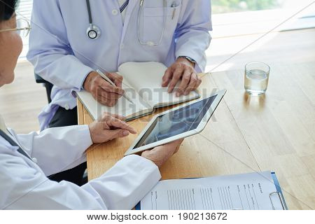 Group of experienced physicians analyzing results of chest X-ray with help of digital tablet, one of them taking necessary notes