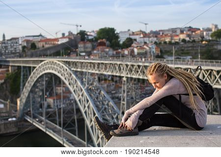 Young beautiful woman with dreadlocks sitting on the background of the bridge of Dom Luis I, Porto, Portugal.