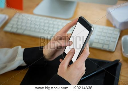 Close-up of woman using mobile phone at desk