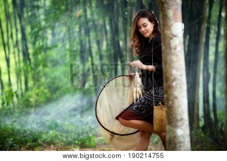 Asian Thai women beautiful in NorthEast Thai traditional dress holding fishes