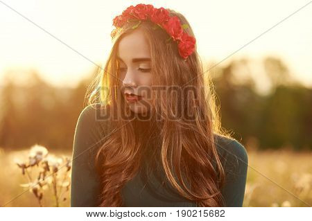 Young, beautiful, attractive model in swimsuit, posing in a field of flowers on the background of sunset, hairstyle, makeup, red corolla with flowers, eyes looking down, portrait.