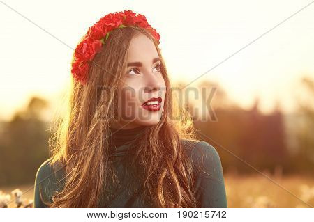 Young, beautiful, attractive woman in swimsuit, posing in a field of flowers on the background of sunset, hairstyle, makeup, red corolla with flowers, model is looking aside, portrait.