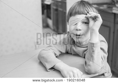 The child was blindfolded at home to make him surprised. Boy peeping from under the blindfold.
