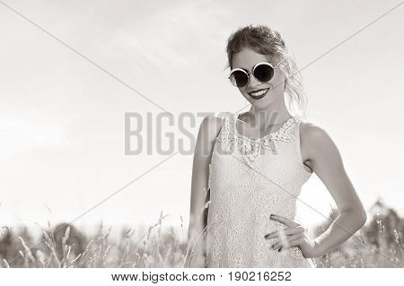 Young, beautiful, attractive model in swimsuit, posing in a field of flowers on the background of sunset, hairstyle, makeup, black and white portrait.