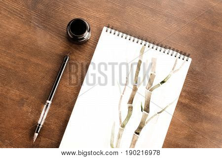 Top View Of Bamboo Drawing In Album And Brush On Table