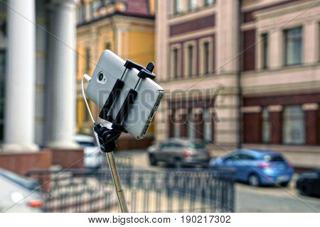 Gray telephone on monopod on the background of city street and road with cars