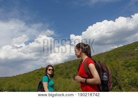 Eco tourism and healthy lifestyle concept. Young hiker girl with backpack Standing under the clouds. Active hikers