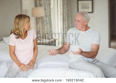 Senior couple sitting on bed and quarrelling with each other