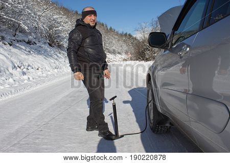Inflating the tire of a Car. Man Car repairs in forest winter. Car pumping air into the wheel. Man uses a bicycle pump. Pumping air into an empty wheel of Man