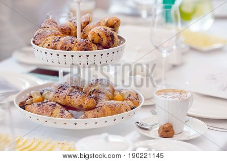 Cappuccino with croissants. Breakfast with coffee and croissants in a basket on table