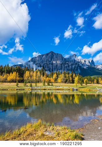 Canmore, near Banff National Park. The concept of recreational tourism. Majestic mountains and scenic cumulus clouds are reflected in the water
