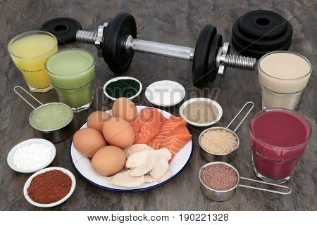 Weight training equipment for body builders with dumbbell weights, high protein meat, fish and dairy with dietary food supplements and drinks.
