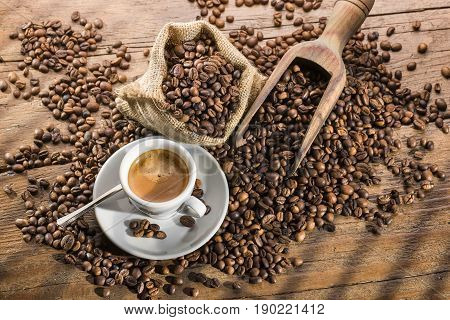 cup of coffee with burlap sack scoop and coffee beans on wooden table illuminated by sunlight coming through the window.