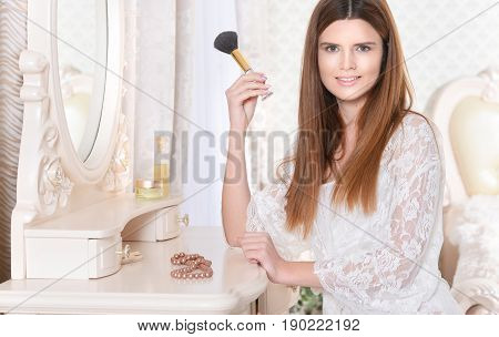 Beautiful young woman sitting at dressing table with brush