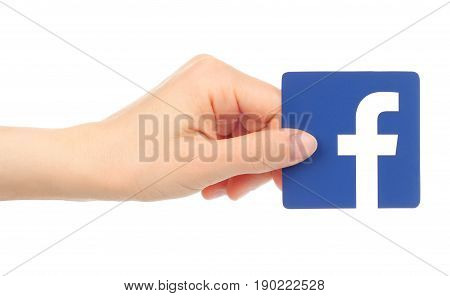 Kiev Ukraine - May 18 2016: Hand holds Facebook icon printed on paper. Facebook is a well-known social networking service