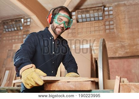 Joiner with grinding machine at carpentry workshop