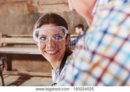 Woman as carpentry trainee smiling and working